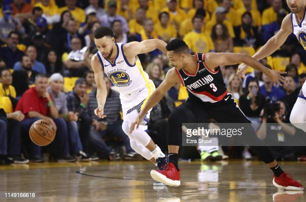 Stephen Curry of the Golden State Warriors battles for a loose ball with CJ McCollum of the Portland Trail Blazers during the first half in game one...