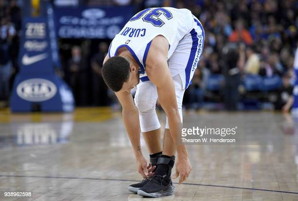 """Stephen Curry of the Golden State Warriors bends over to tie his Under Armour """"Pi Day"""" Curry 5 shoe he wore against the Atlanta Hawks during an NBA..."""
