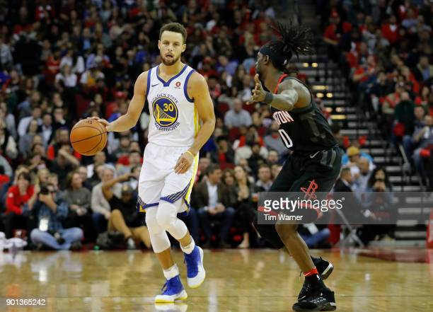 Stephen Curry of the Golden State Warriors brings the ball down the court defended by Briante Weber of the Houston Rockets in the second half at...