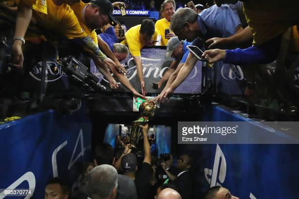 Stephen Curry of the Golden State Warriors carries off the Larry O'Brien Championship Trophy after defeating the Cleveland Cavaliers 129120 in Game 5...