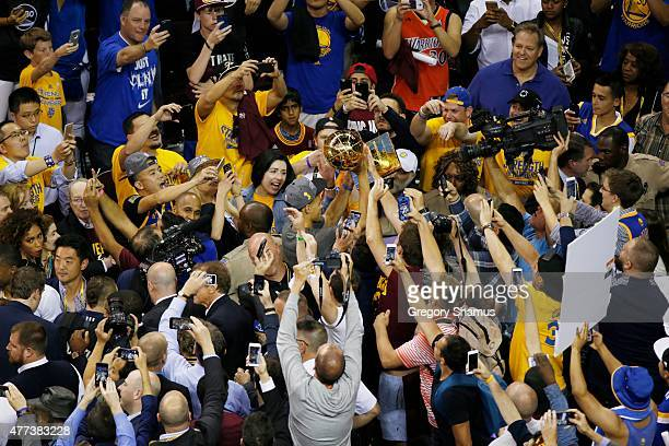 Stephen Curry of the Golden State Warriors carries out the Larry O'Brien Championship Trophy after the win against the Cleveland Cavaliers for Game...
