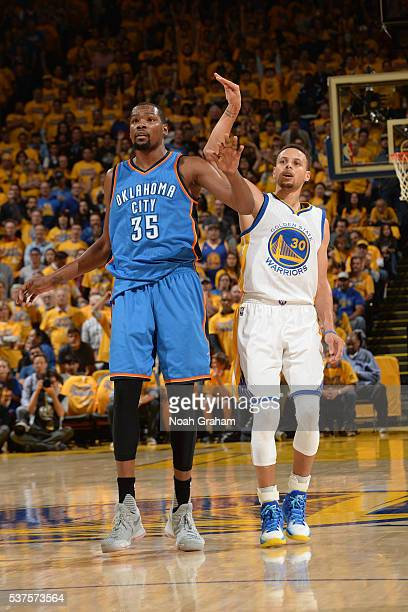 Stephen Curry of the Golden State Warriors celebrates a three point basket as Kevin Durant of the Oklahoma City Thunder guards him in Game Five of...