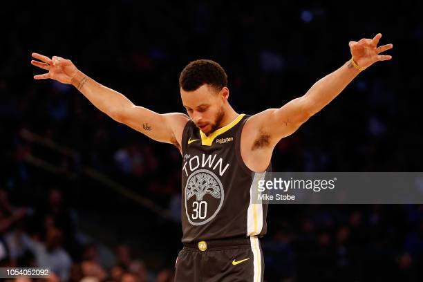 Stephen Curry of the Golden State Warriors celebrates after teammate Alfonzo McKinnie hits a three point basket against the New York Knicks during...