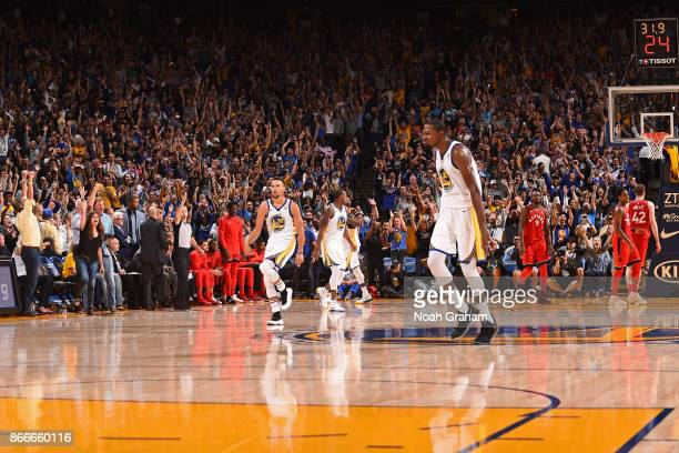 Stephen Curry of the Golden State Warriors celebrates as he runs up court after making the game winning shot against the Toronto Raptors on October...