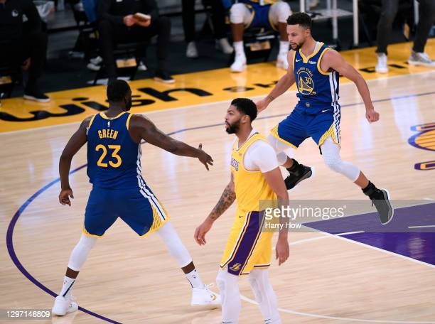 Stephen Curry of the Golden State Warriors celebrates his three pointer with Draymond Green, in front of Anthony Davis of the Los Angeles Lakers,...