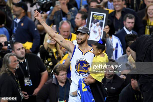 Stephen Curry of the Golden State Warriors celebrates holding his daughter Ryan after defeating the Cleveland Cavaliers 129120 in Game 5 to win the...