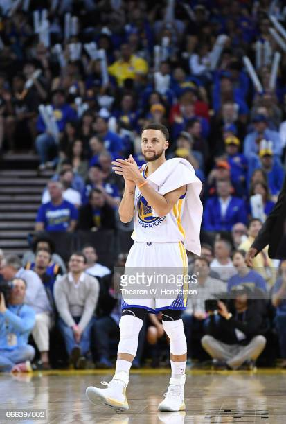 Stephen Curry of the Golden State Warriors celebrates off the bench after they scored a basket against the Minnesota Timberwolves during an NBA...