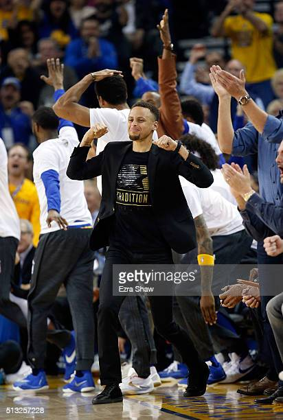 Stephen Curry of the Golden State Warriors celebrates on the bench after the Warriors scored a basket against the Atlanta Hawks at ORACLE Arena on...