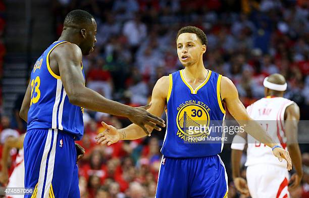 Stephen Curry of the Golden State Warriors celebrates with Draymond Green after setting the record for most three pointers in a post season in the...