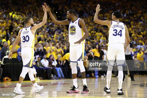 Stephen Curry of the Golden State Warriors celebrates with Kevin Durant and Shaun Livingston against the Cleveland Cavaliers in overtime during Game...