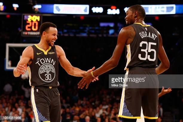 Stephen Curry of the Golden State Warriors celebrates with teammate Kevin Durant after hitting a three point basket against the New York Knicks...