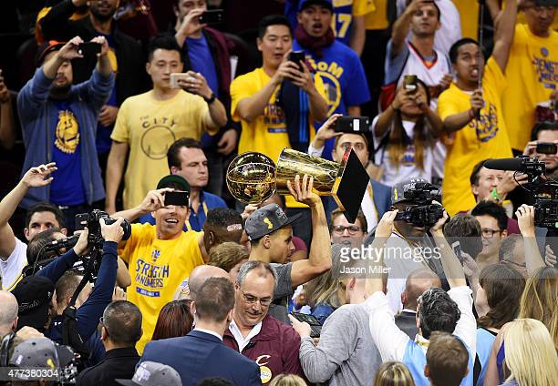 Stephen Curry of the Golden State Warriors celebrates with the Larry O'Brien NBA Championship Trophy after defeating the Cleveland Cavaliers in Game...