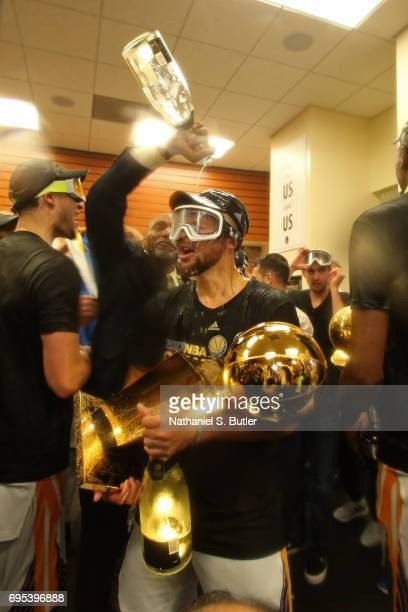 Stephen Curry of the Golden State Warriors celebrates with the Larry O'Brien Trophy in the locker room after winning the NBA Championsip in Game Five...