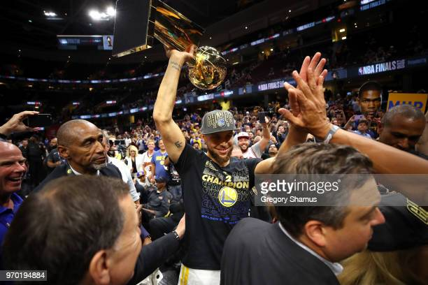 Stephen Curry of the Golden State Warriors celebrates with the Larry O'Brien Trophy after defeating the Cleveland Cavaliers during Game Four of the...