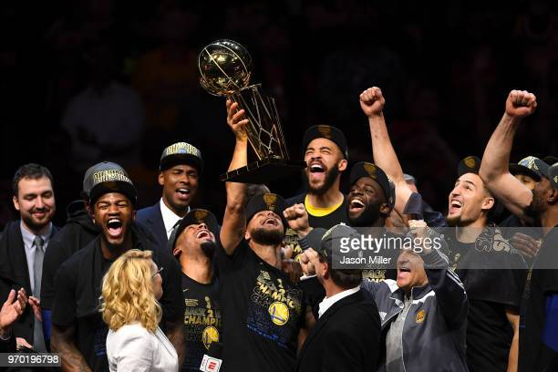 Stephen Curry of the Golden State Warriors celebrates with the Larry O'Brien Trophy after defeating the Cleveland Cavaliers in Game Four of the 2018...