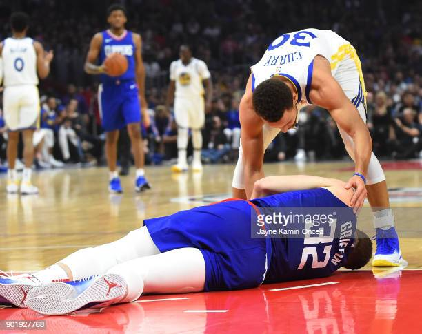 Stephen Curry of the Golden State Warriors checks on Blake Griffin of the Los Angeles Clippers as he lays on the court after he sustained a...