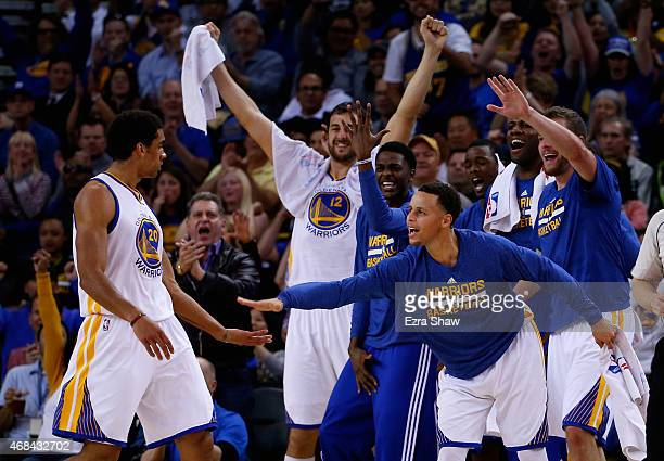 Stephen Curry of the Golden State Warriors congratulates James Michael McAdoo after he made a shot and was fouled during their game against the...