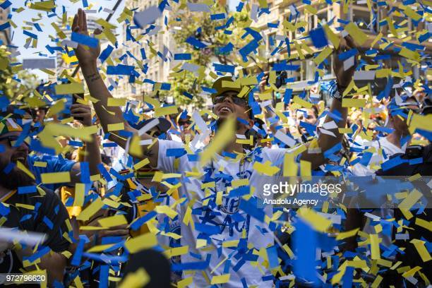 Stephen Curry of the Golden State Warriors delights in falling confettis as he interacts with fans along the parade route during the the Golden State...