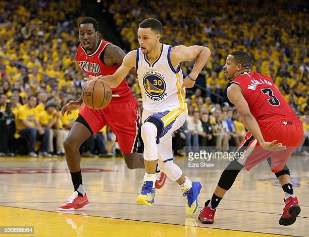 Stephen Curry of the Golden State Warriors dribbles between AlFarouq Aminu and CJ McCollum of the Portland Trail Blazers during Game Five of the...