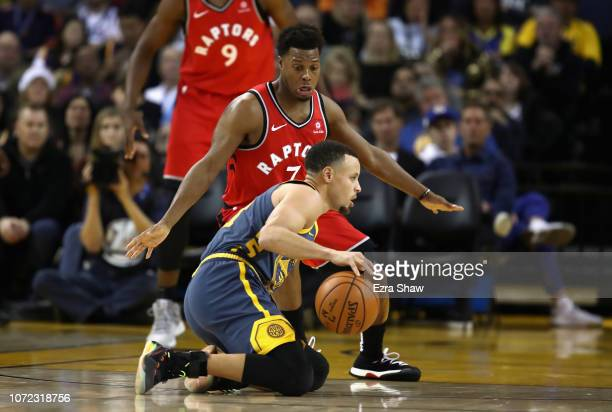 Stephen Curry of the Golden State Warriors dribbles on his knees while being guarded by Kyle Lowry of the Toronto Raptors at ORACLE Arena on December...
