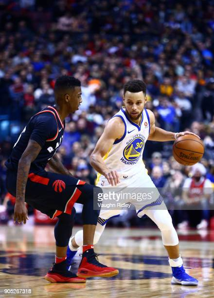 Stephen Curry of the Golden State Warriors dribbles the ball as Delon Wright of the Toronto Raptors defends during the second half of an NBA game at...