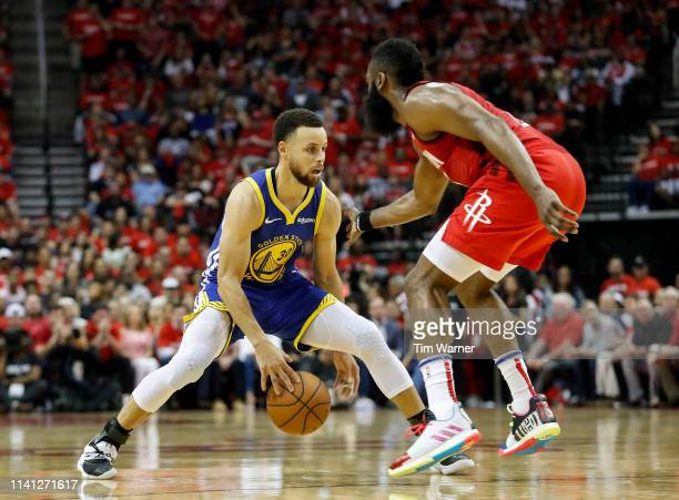 Stephen Curry of the Golden State Warriors dribbles the ball defended by James Harden of the Houston Rockets in the fourth quarter during Game Three...