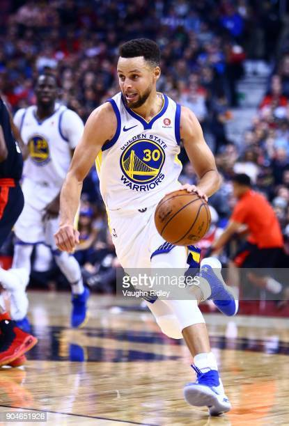 Stephen Curry of the Golden State Warriors dribbles the ball during the second half of an NBA game against the Toronto Raptors at Air Canada Centre...