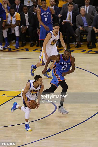 Stephen Curry of the Golden State Warriors dribbles the ball up court while guarded by Kevin Durant of the Oklahoma City Thunder in Game Five of the...