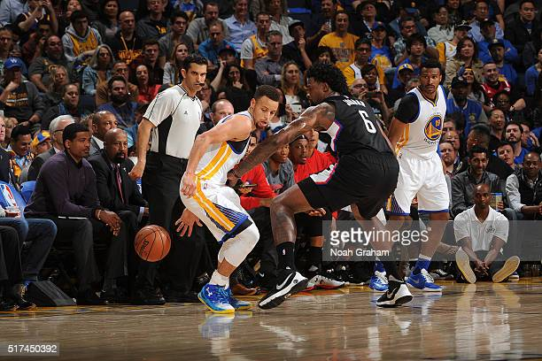 Stephen Curry of the Golden State Warriors dribbles the ball while guarded by DeAndre Jordan of the Los Angeles Clippers on March 23 2016 at Oracle...