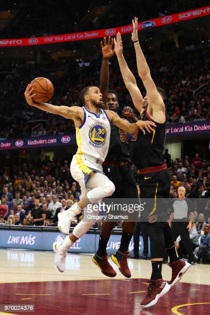 Stephen Curry of the Golden State Warriors drive to the basket against Jeff Green and Larry Nance Jr #22 of the Cleveland Cavaliers in the first...