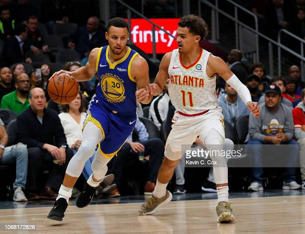 Stephen Curry of the Golden State Warriors drives against Trae Young of the Atlanta Hawks at State Farm Arena on December 3 2018 in Atlanta Georgia...