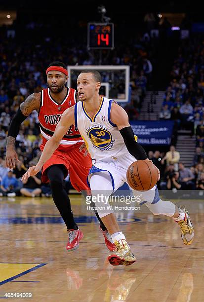 Stephen Curry of the Golden State Warriors drives past Mo Williams of the Portland Trail Blazers at ORACLE Arena on January 26 2014 in Oakland...