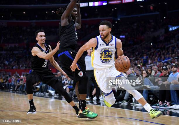 Stephen Curry of the Golden State Warriors drives past Montrezl Harrell and Landry Shamet of the LA Clippers during a 113105 Warrior win in Game Four...
