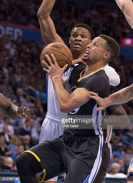 Stephen Curry of the Golden State Warriors drives past Russell Westbrook of the Oklahoma City Thunder for two points during the first quarter of a...