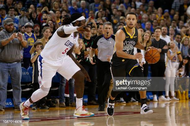 Stephen Curry of the Golden State Warriors drives to the basket and makes the gamewinning shot against Montrezl Harrell of the LA Clippers at ORACLE...