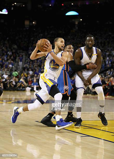Stephen Curry of the Golden State Warriors drives to the basket as Draymond Green of the Golden State Warriors sets a pick on Russell Westbrook of...