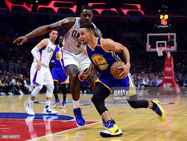 Stephen Curry of the Golden State Warriors drives to the basket in front of DeAndre Jordan of the LA Clippers at Staples Center on December 7 2016 in...