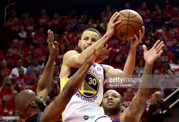 Stephen Curry of the Golden State Warriors drives to the basket in the second half against Chris Paul and PJ Tucker of the Houston Rockets in Game...