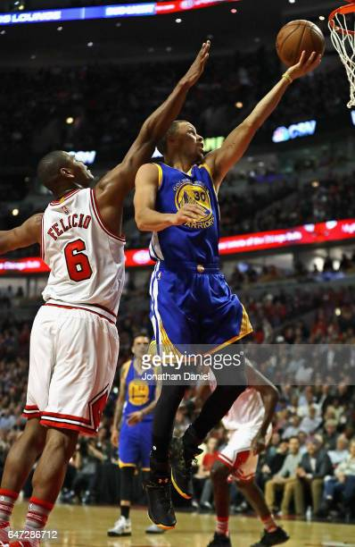 Stephen Curry of the Golden State Warriors drives to the basket past Cristiano Felicio of the Chicago Bulls at the United Center on March 2, 2017 in...