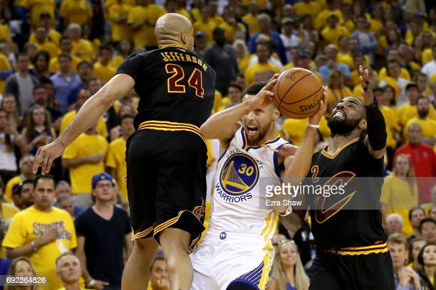 Stephen Curry of the Golden State Warriors drives to the hoop against Richard Jefferson and Kyrie Irving of the Cleveland Cavaliers in Game 2 of the...