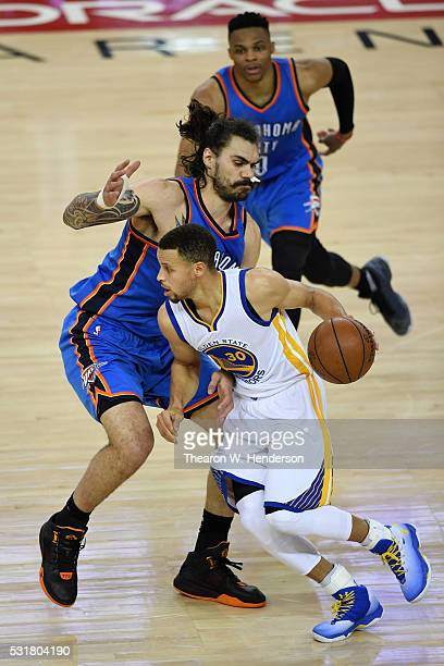 Stephen Curry of the Golden State Warriors drives with the ball against Steven Adams of the Oklahoma City Thunder during game one of the NBA Western...