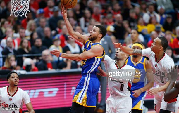 Stephen Curry of the Golden State Warriors drives with the ball against Damian Lillard of the Portland Trail Blazers during Game Four of the Western...