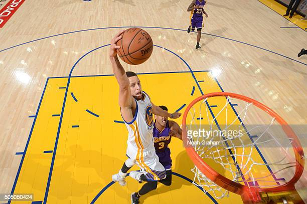 Stephen Curry of the Golden State Warriors dunks against Anthony Brown of the Los Angeles Lakers on January 14 2016 at Oracle Arena in Oakland...