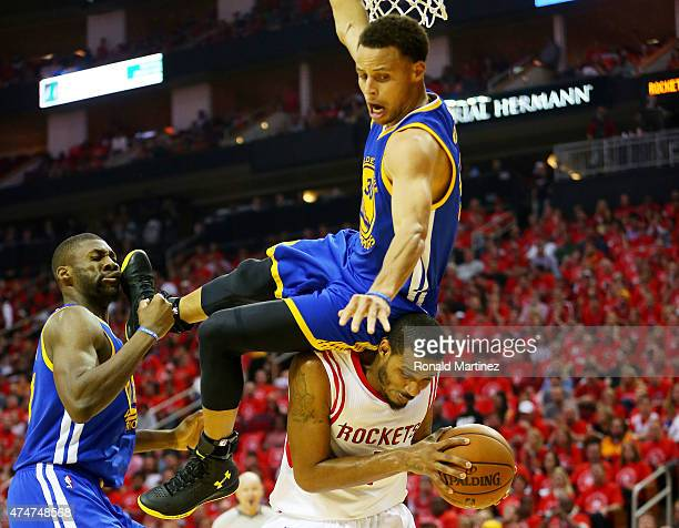 Stephen Curry of the Golden State Warriors falls over Trevor Ariza of the Houston Rockets on his way to an injury in the second quarter during Game...