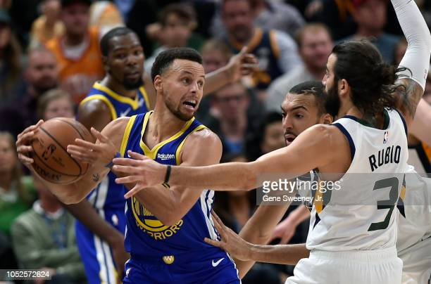 Stephen Curry of the Golden State Warriors fights off defenders Ricky Rubio and Rudy Gobert of the Utah Jazz in the second half of a NBA game at...
