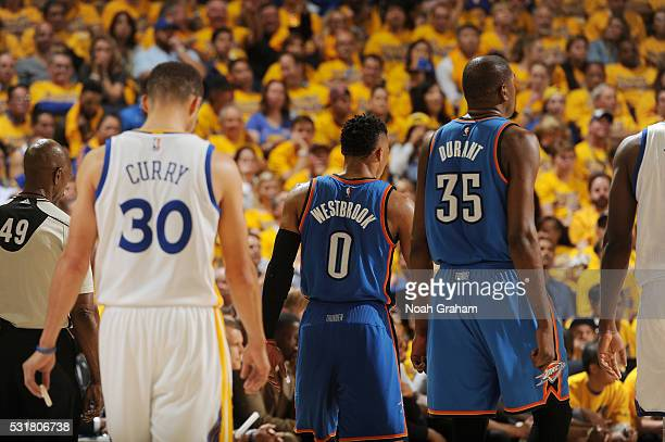 Stephen Curry of the Golden State Warriors follows off the court Russell Westbrook and Kevin Durant of the Oklahoma City Thunder during Game One of...