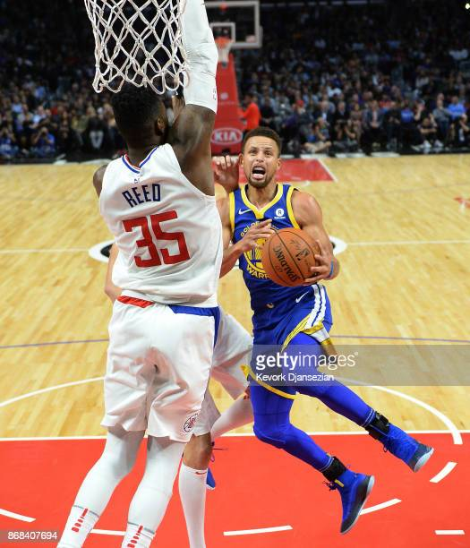Stephen Curry of the Golden State Warriors get fouled by Willie Reed of the Los Angeles Clippers as he drives it the basket battle during the second...