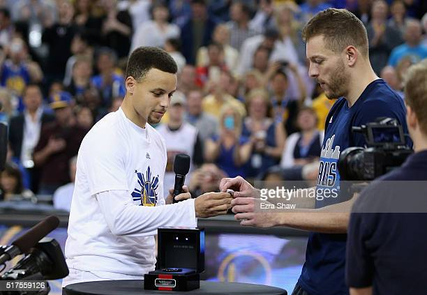 Stephen Curry of the Golden State Warriors gives David Lee of the Dallas Mavericks his championship ring from last season before their game at ORACLE...