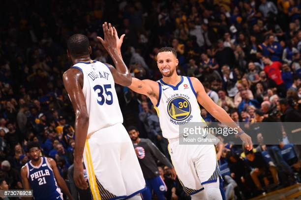 Stephen Curry of the Golden State Warriors gives high five to Kevin Durant of the Golden State Warriors during the game against the Philadelphia...