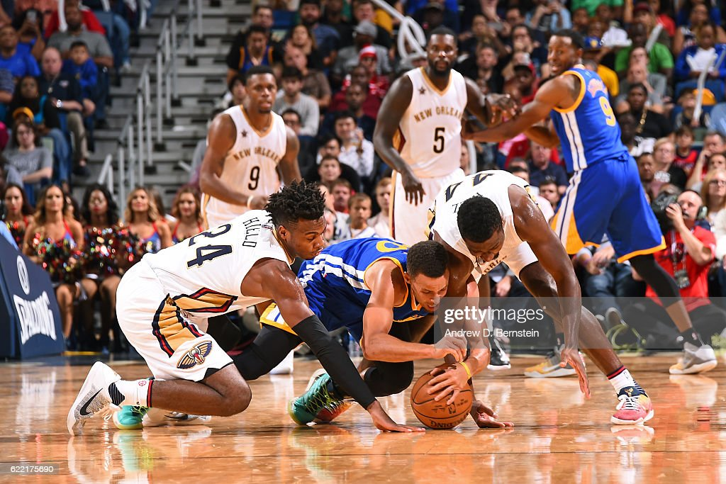Stephen Curry #30 of the Golden State Warriors goes after a loose ball against Buddy Hield #24 and Solomon Hill #44 of the New Orleans Pelicans during a game at Smoothie King Center on October 28, 2016 in New Orleans, Louisiana.